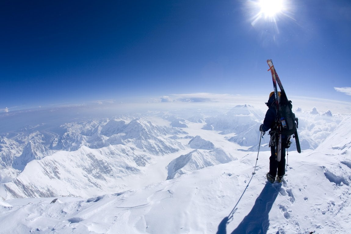 Snow sky athlete looking down a mountain